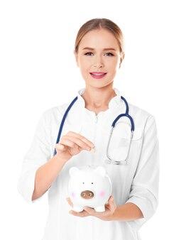화이트에 돼지 저금통에 동전을 넣어 젊은 여성 의사