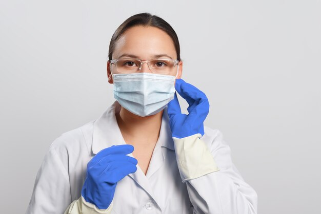 Young female doctor putting on a protective mask on her face.