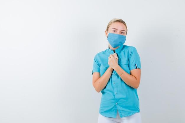 医療制服で懇願するジェスチャーで握りしめられた手を示す若い女性医師