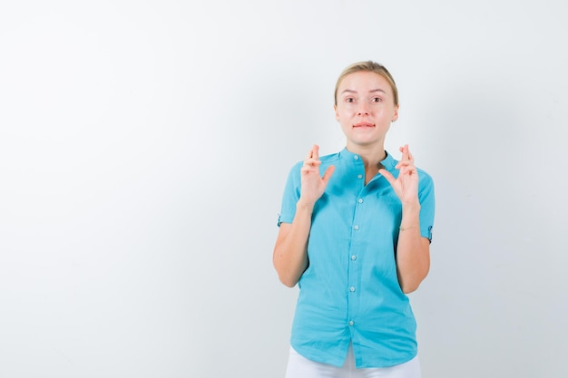医療制服、マスク、躊躇しているように見える交差した指を示す若い女性医師