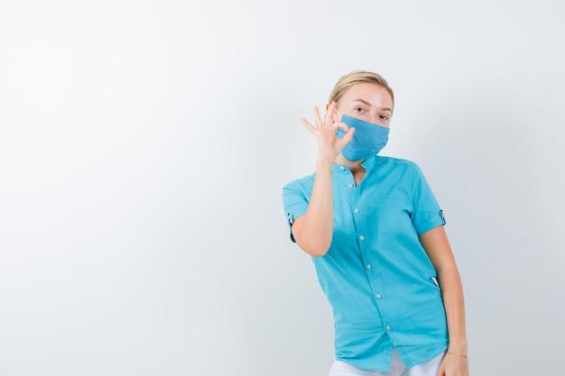Giovane dottoressa che mostra gesto ok in uniforme medica, maschera e sembra allegra