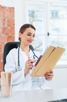 Молодая женщина-врач сидит за столом перед окном в клинике, читая файл или досье