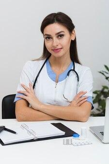 Giovane medico femmina seduto con le mani incrociate
