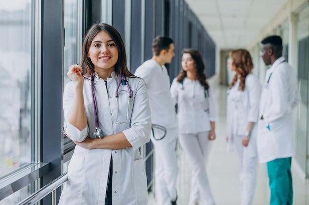 Молодая женщина-врач стоит в коридоре больницы
