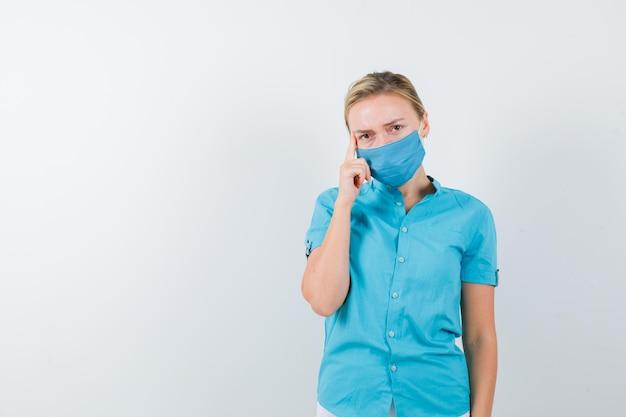 孤立した制服でポーズを考えて立っている若い女性医師