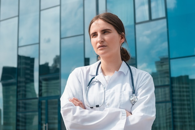 Young female doctor standing outside the hospital close up