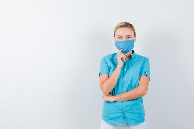 Giovane dottoressa in piedi in posa di pensiero in uniforme e guardando pensierosa