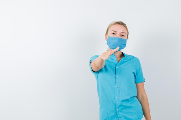 制服を着て挨拶し、自信を持って見えるために手を伸ばす若い女性医師
