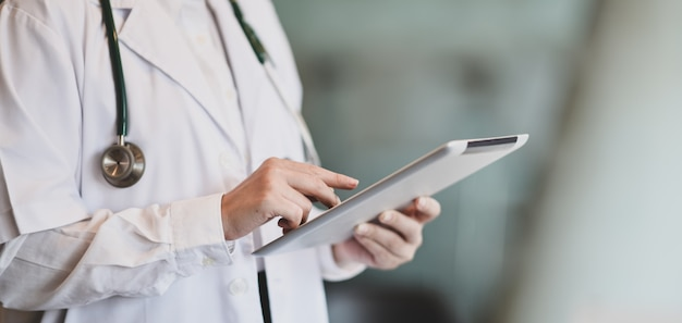 Young female doctor summarises patient charts with digital tablet