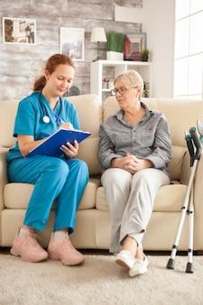 요양원에서 노인 여성과 대화를 나누는 동안 클립보드에 메모를 하는 젊은 여성 의사.