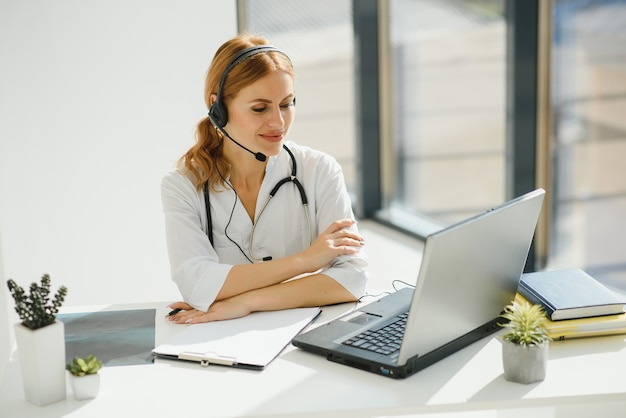 Young female doctor talking to patient online from medical office. physician consulting client on video chat laptop at hospital