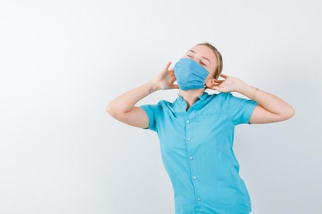 Giovane dottoressa in uniforme che si tiene per mano dietro la testa e sembra assonnata isolata