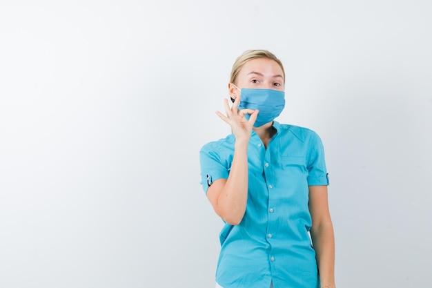 Giovane dottoressa in uniforme che mostra gesto ok e sembra sicura isolata
