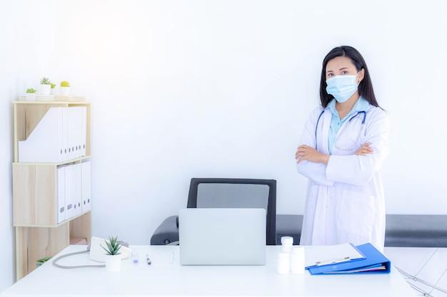彼女のオフィスで働いている間フェイスマスクを身に着けている若い女性医師。ヘルスケアと医療の概念。