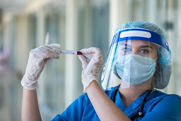 긍정적 인 결과를 가진 혈액 샘플로 테스트 튜브를 들고 얼굴 방패를 착용하는 젊은 여성 의사 covid-19