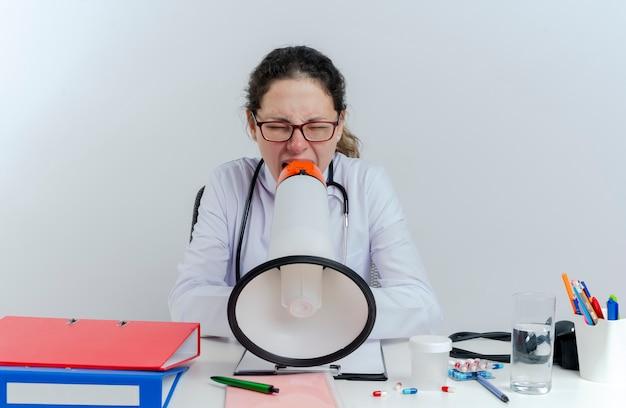 의료 가운 및 청진 기 및 의료 도구 격리 된 닫힌 된 눈으로 시끄러운 스피커에서 소리와 함께 책상에 앉아 안경을 착용하는 젊은 여성 의사