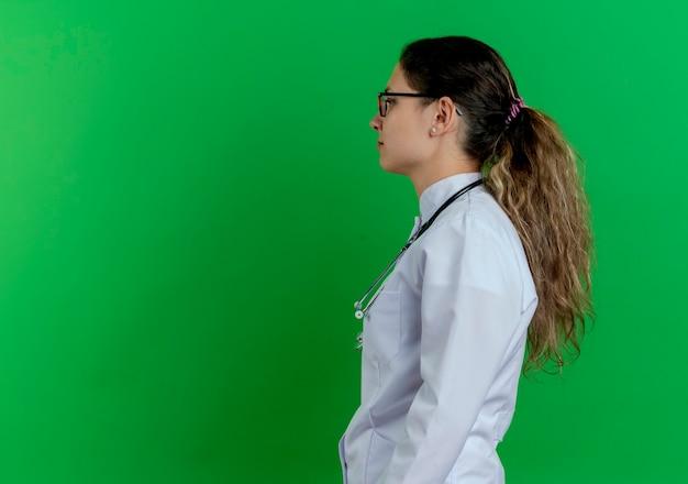 医療ローブと聴診器と眼鏡を身に着けている若い女性医師は、コピースペースと緑の壁にまっすぐに分離された縦断ビューで立っています