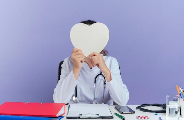 의료 가운과 청진기를 착용하고 고립 된 심장 모양 뒤에 의료 도구를 들고 책상에 앉아 젊은 여성 의사