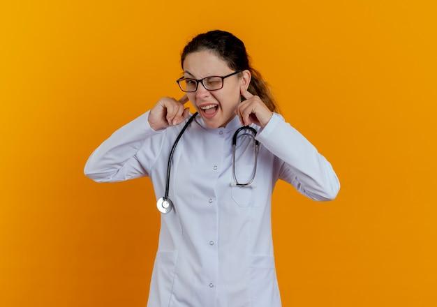 隔離された眼鏡をかけた医療ローブと聴診器を身に着けている若い女性医師