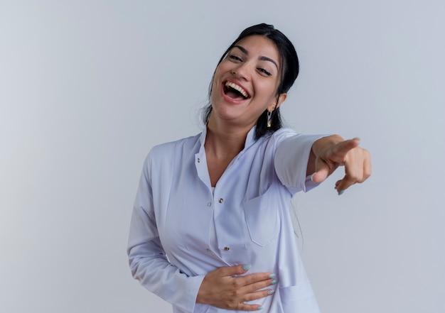 Giovane medico femminile che indossa abito medico guardando rivolto dritto e ridendo isolato