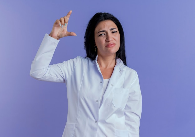 Young female doctor wearing medical robe looking showing amount gesture