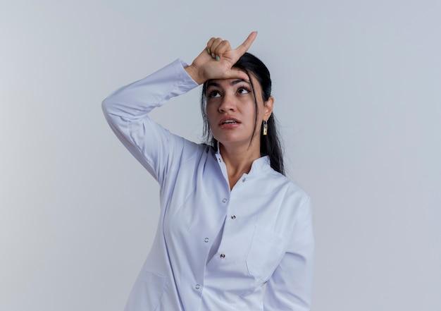 Giovane medico femminile che indossa abito medico alzando lo sguardo facendo gesto perdente isolato