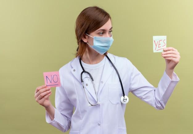 의료 가운, 마스크 및 청진기를 착용하고 예 및 아니오 메모를 들고 격리 된 녹색 벽에 예 메모를보고 젊은 여성 의사