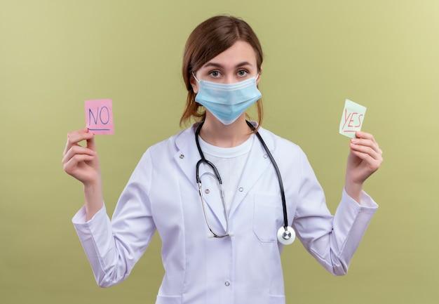 의료 가운, 마스크 및 청진기를 착용하고 예 및 아니오 메모를 들고 고립 된 녹색 벽에 찾고 젊은 여성 의사