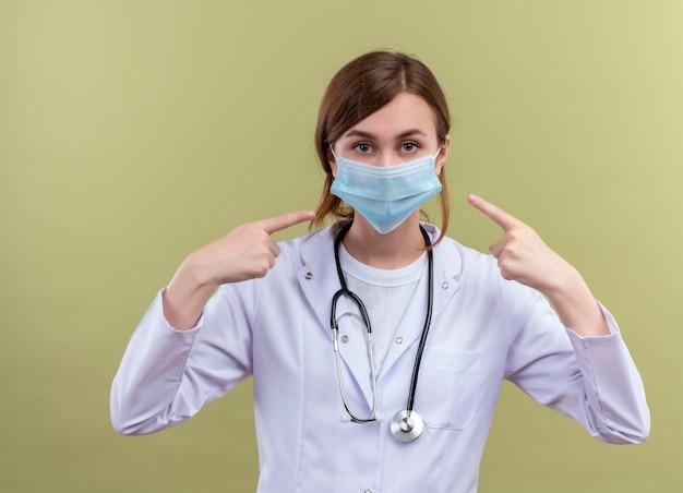의료 가운, 마스크 및 격리 된 녹색 벽에 그녀의 마스크를 가리키는 청진기를 착용하는 젊은 여성 의사