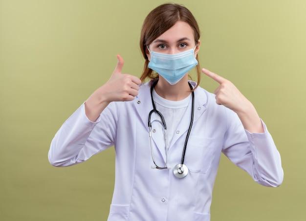 의료 가운, 마스크 및 청진기를 착용하고 엄지 손가락을 표시하고 격리 된 녹색 벽에 그녀의 마스크를 가리키는 젊은 여성 의사