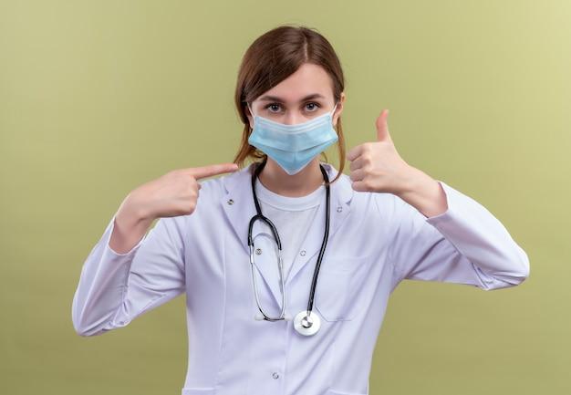 의료 가운, 마스크 및 청진기를 착용하고 엄지 손가락을 보여주는 젊은 여성 의사와 격리 된 녹색 벽에 가리키는