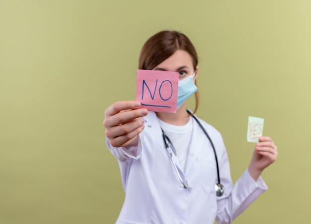コピースペースのある孤立した緑の壁にメモを伸ばす医療ローブ、マスク、聴診器を身に着けている若い女性医師