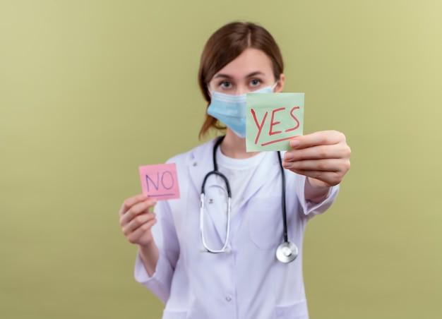 Giovane medico femminile che indossa veste medica, maschera e stetoscopio che allunga sì nota sulla parete verde isolata con lo spazio della copia