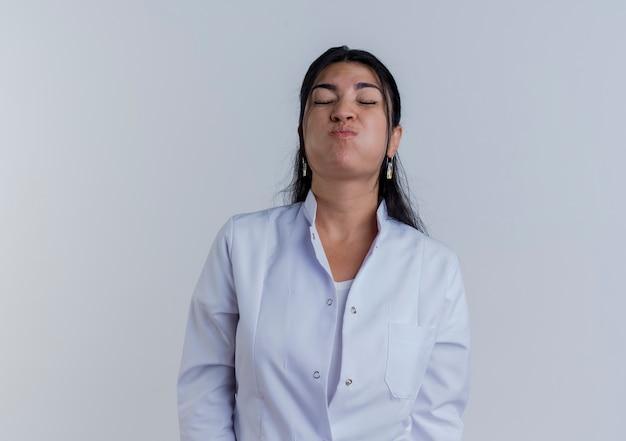 Giovane medico femminile che indossa guance sbuffanti veste medica con gli occhi chiusi isolati