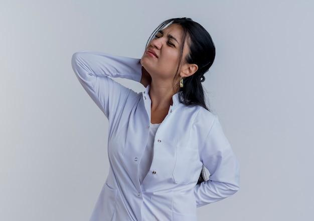 首の後ろと背中の後ろに手を置いて医療ローブを身に着けている若い女性医師は、孤立した目を閉じて痛みに苦しんでいます
