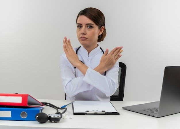Young female doctor wearing medical robe with stethoscope sitting at desk work on computer with medical tools gesturing no on isolated white wall with copy space
