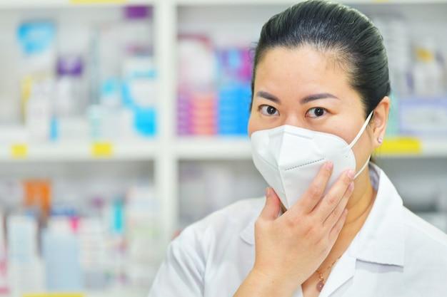 多くの薬棚に温度計と聴診器でn95マスクを身に着けている若い女性医師。コロナウイルス(covid-19)病気、インフルエンザの治療と保護の概念。