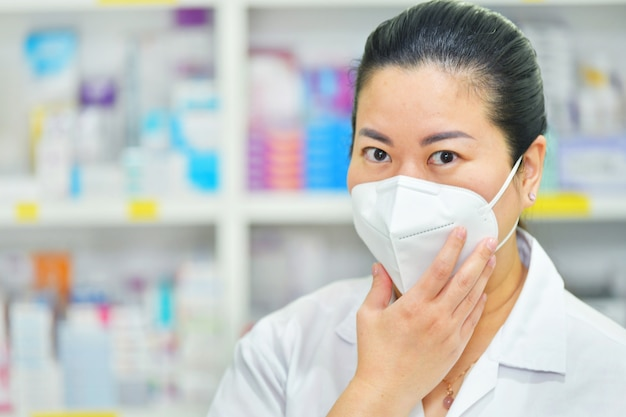 Young female doctor wearing n95 mask with thermometer and stethoscope on many medicine shelf. coronavirus (covid-19)concept of disease, flu treatment and protection.