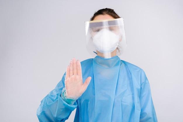 Ppeを身に着けている若い女性医師は、白でコロナウイルスの世界的大流行の写真を広めるのをやめます