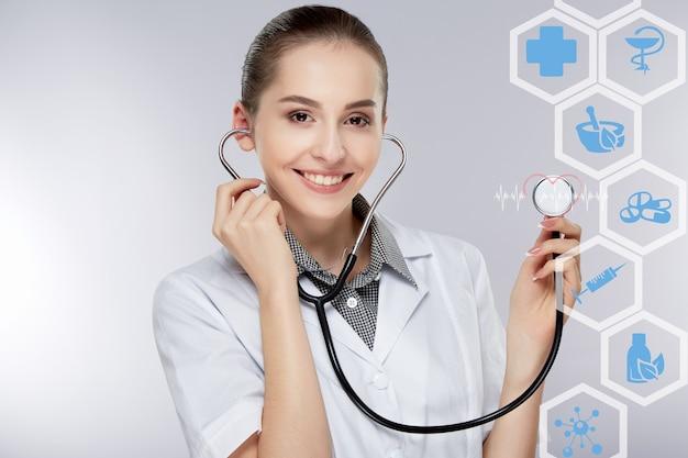 회색 스튜디오 배경에서 귀에 흰색 의료 유니폼과 청진기를 입고 젊은 여성 의사. 의사는 청진기를 통해 청력, 카메라를보고 웃고