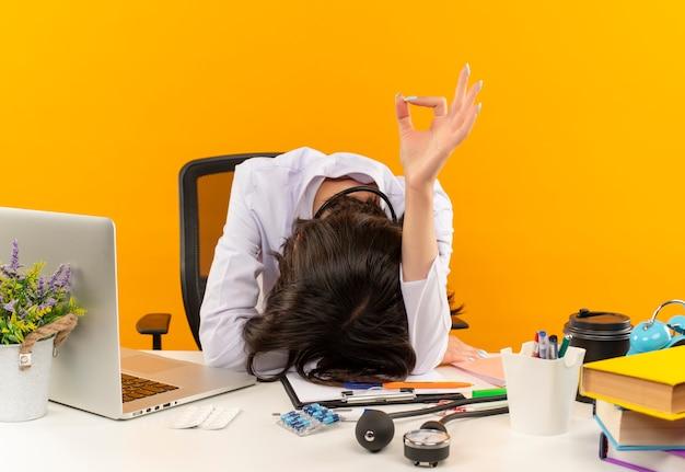 Giovane medico femminile in camice bianco che dorme sul tavolo con laptop e documenti che mostrano segno giusto sopra la parete arancione