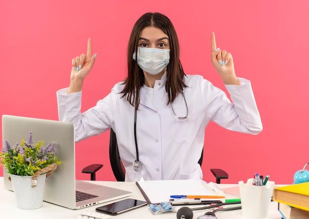 Giovani donne medico in camice bianco con maschera protettiva per il viso e uno stetoscopio intorno al collo rivolto verso l'alto con le dita indice seduto al tavolo con il computer portatile sulla parete rosa