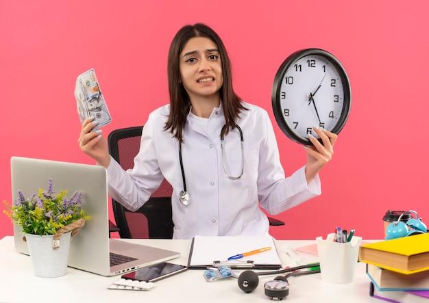 Giovane medico femminile in camice bianco con lo stetoscopio intorno al collo che tiene contanti e orologio da parete che sembra confuso e molto ansioso seduto al tavolo con il computer portatile sul muro rosa