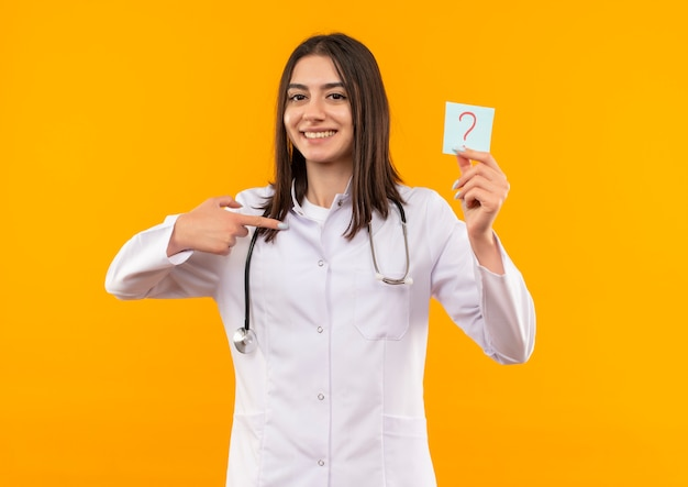 Young female doctor in white coat with stethoscope around her neck holding reminder paper with question mark pointing with finger to it smiling looking to the front standing over orange wall