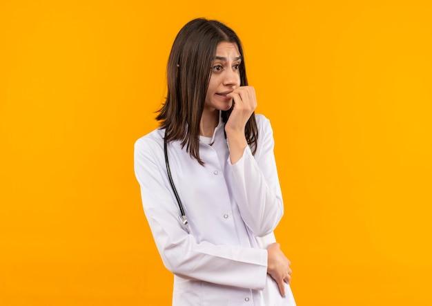 Giovane medico femminile in camice bianco con lo stetoscopio intorno al collo che osserva da parte in piedi stressato e nervoso sopra la parete arancione