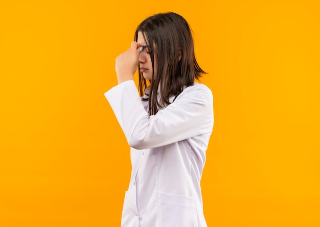 Giovane medico femminile in camice bianco con lo stetoscopio intorno al collo che sembra stanco e sovraccarico di lavoro in piedi sopra la parete arancione