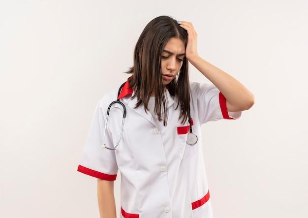 Giovane medico femminile in camice bianco con lo stetoscopio intorno al collo che sembra stanco e sovraccarico di lavoro in piedi sopra il muro bianco