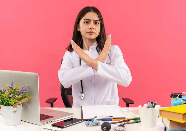 Young female doctor in white coat with stethoscope around her neck making stop sign with serious face crossing hands sitting at the table with laptop over pink wall
