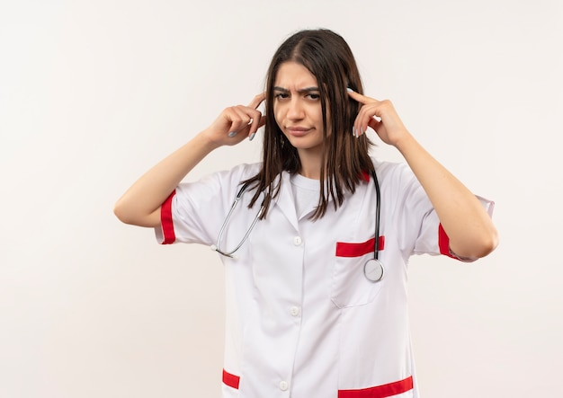 Giovane dottoressa in camice bianco con lo stetoscopio intorno al collo che punta le tempie cercando stanco e annoiato in piedi sopra il muro bianco