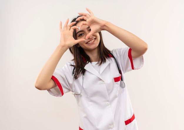 Giovane medico femminile in camice bianco con lo stetoscopio intorno al collo che mostra il gesto del cuore sorridente in piedi amichevole sopra il muro bianco